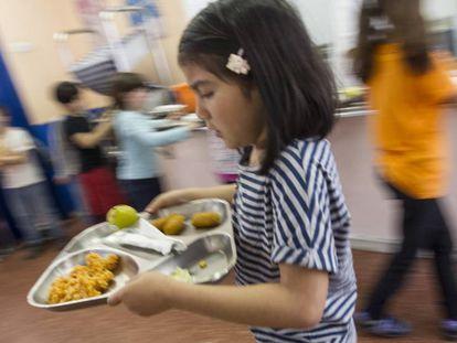 Una niña lleva una bandeja de comida en un colegio de Barcelona