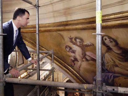 El Príncipe Felipe contempla las obras del pintor de Fuendetodos desde un andamio.