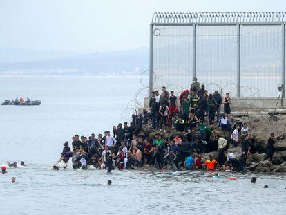 Inmigrantes irregulares en el espigón de la frontera entre Ceuta y Marruecos, este martes.
