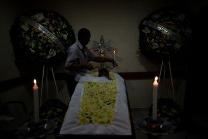 Conductor del Ayuntamiento adorna un cadáver antes del entierro.