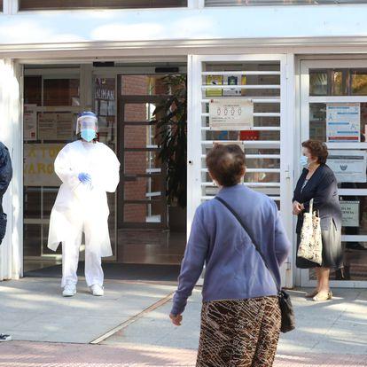Una sanitaria sale a atender a numerosas personas que hacen cola en el Centro de Salud Vicálvaro-Artilleros, este lunes