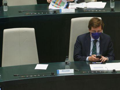 El alcalde de Madrid, José Luis Martínez-Almeida, consulta el móvil durante el pleno del Ayuntamiento de Madrid.