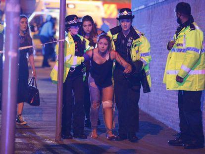 Una joven herida es atendida por miembros de la policía tras el atentado ocurrido durante el concierto de Ariana Grande en el Manchester Arena.