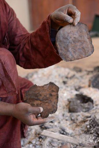 Un hombre muestra fragmentos de un texto quemado en el Centro de Documentación de Ahmed Baba, en Tombuctú, el lunes tras la huida de los islamistas.