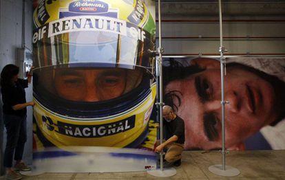 Operarios cuelgan fotos del brasileño Ayrton Senna en una exposición conmemorativa en la pista de carreras de Imola (Italia) en 2014.