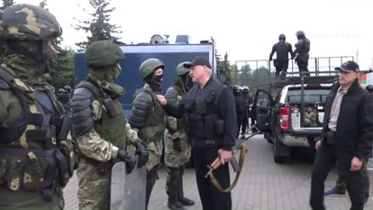 Lukashenko, con un rifle, habla con antidisturbios frente a una protesta por la democracia el pasado 23 de agosto en Minsk.
