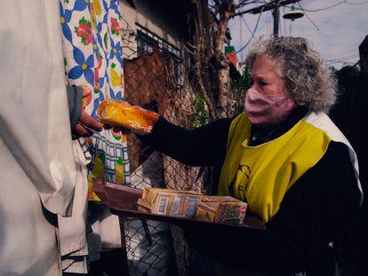 Una voluntaria de Hogar de Cristo entrega alimentos de primera necesidad en un barrio popular argentino.