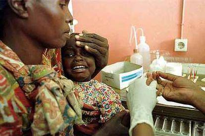 Una mujer sostiene a su hija, enferma de malaria, en el hospital mozambiqueño de Manhiça.