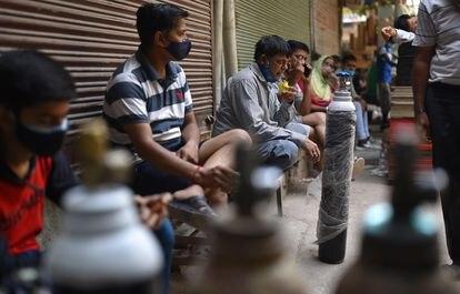 Varias personas esperan para rellenar sus botellas de oxígeno en una tienda de Nueva Delhi.