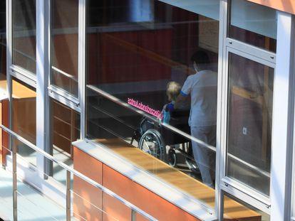 Una trabajadora traslada a una interna de una residencia madrileña.