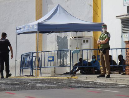 Un policía y un guarda de seguridad vigilan a un grupo de inmigrantes indocumentados que saltaron la valla de Melilla en agosto del año pasado.