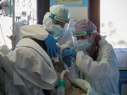 Una doctora y una enfermera de la Unidad de Cuidados Intensivos del Hospital Morales Meseguer de Murcia cambian el respirador a un paciente ingresado por covid-19, en enero de este año.