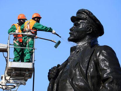 Unos trabajadores limpian una escultura monumental de Lenin en Krasnoyarsk (Rusia), este martes.