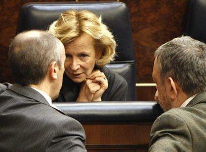 La vicepresidenta económica del Gobierno, Elena Salgado, conversa con dos diputados en su escaño del Parlamento.
