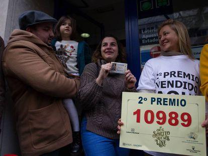 Sandra, junto a su Óscar y su hija Sofía, muestra el décimo premiado ante la mirada de la lotera Carmen Hinojosa Navas.
