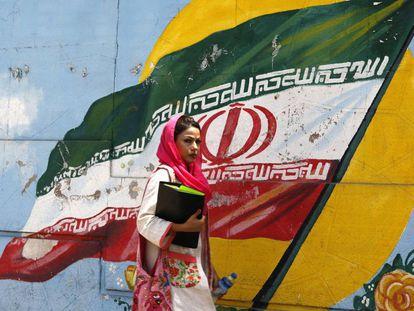 Una iraní pasa ante un mural con la bandera nacional en Teherán.