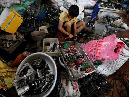 Un chico clasifica piezas reciclables de equipos eléctricos y electrónicos en la aldea de Quan Do, en la provincia de Bac Ninh, Vietnam, el 1 de julio de 2020.