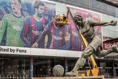 Retirada del póster de Messi de las instalaciones del Camp Nou, en la mañana de este martes, poco antes de que el delantero firmase con el PSG tras abandonar el Barcelona.
