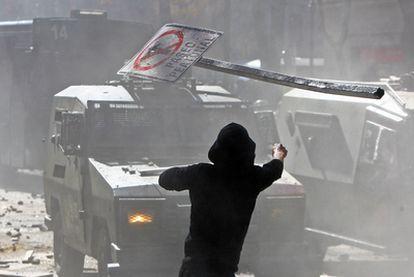 Un estudiante lanza una señal de tráfico contra la policía durante las protestas en Santiago.