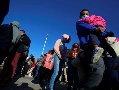 Migrantes hacen fila el viernes 19 de febrero en el puerto de entrada de El Chaparral, que divide Tijuana y San Diego.