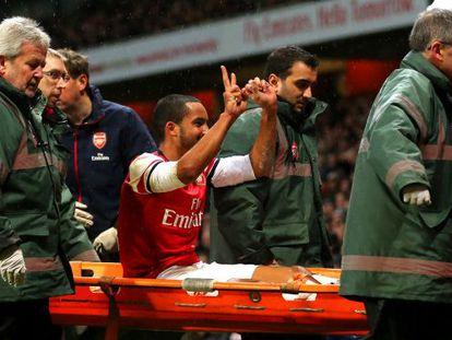 Walcott se dirige a los hinchas del Tottenham al salir en camilla.