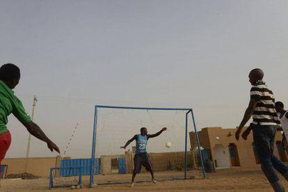 Unos emigrantes juegan al fútbol en el patio central de un centro de acogida de emigrates de la OIM