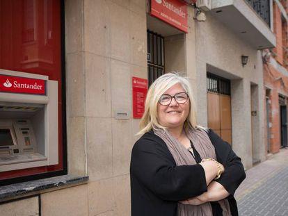 La alcaldesa de Castellnovo (Castellón), Carmina Gil, ante el único y último banco de su municipio, que acaba de echar el cierre.