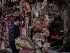 A vendor selling dried fish works at his stall at a market in Wuhan, central China's Hubei province on January 15, 2021. (Photo by NICOLAS ASFOURI / AFP)