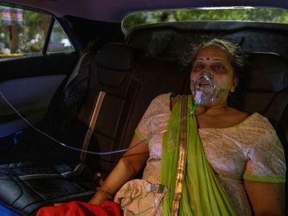 Una mujer con problemas respiratorios recibía oxígeno de forma gratuita desde su coche, en Ghaziabad, India, el pasado 24 de abril.