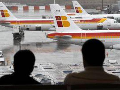 Dos pasajeros observan varios aviones de la compañia Iberia en las pistas del aeropuerto de Barajas. EFE/Archivo