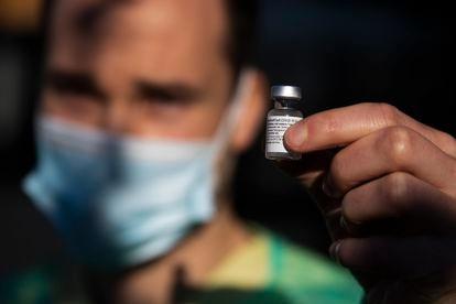 Un sanitario gallego sostiene una vacuna.