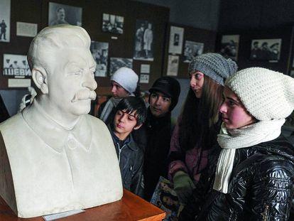 Niños y adolescentes georgianos miran el busto de Stalin en el museo dedicado al líder soviético en Gori.