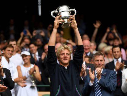 Davidovich alza el trofeo de campeón júnior en Wimbledon.