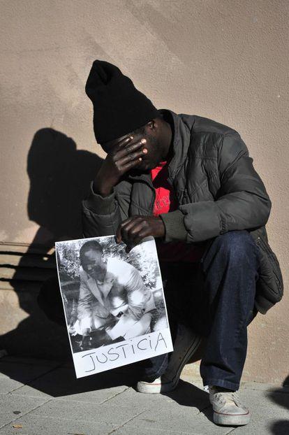 Un senegalés con la foto de su compatriota asesinado.