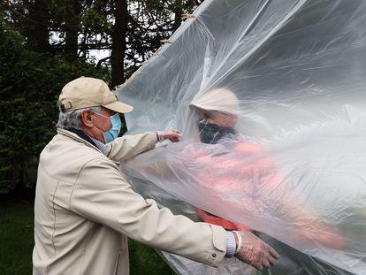 Un hombre abraza a su padre a través de un plástico en la celebración del día de los caídos en Wantagh, Nueva York, este domingo.
