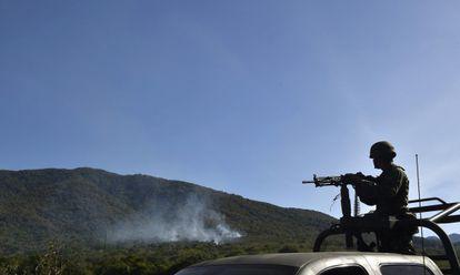 Un soldado junto a un helicóptero derribado en Jalisco.