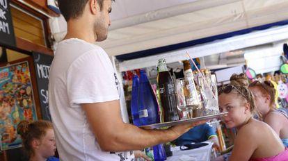 Un camarero sirve a un grupo de turistas en un restaurante en la Alcudia, Mallorca.