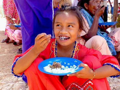 Una niña come arroz con chivo en la comunidad indígena wayúu del Guayabal, en Colombia.