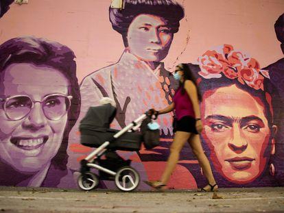 Una mujer camina junto al mural restaurado de las mujeres del barrio de Ciudad Lineal en Madrid, este sábado.