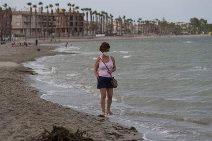 Una vecina de Los Alcázares camina por la orilla del mar Menor.