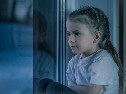 Una niña piensa apoyada en la ventana.