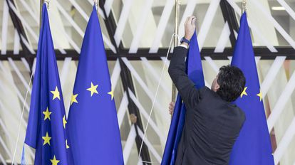 Una persona coloca banderas de Europa en la sede del Consejo Europeo.