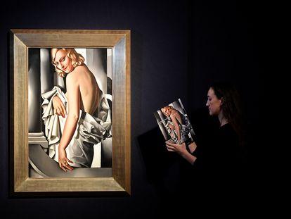 Una empleada de Christie's revisa un catálogo junto a 'Retrato de Marjorie Ferry, de Tamara de Lempecka.