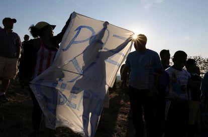 Varios manifestantes sujetan una pancarta pidiendo 'Paz' en la frontera entre Venezuela y Brasil.
