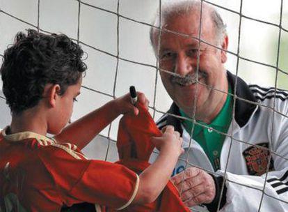 Del Bosque firma una gorra a un niño tras un entrenamiento de la selección
