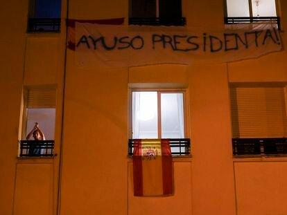 Vecinos celebran la victoria de Ayuso en el edificio de enfrente de la sede del PSOE en la calle Ferraz de Madrid.
