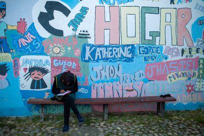 Una joven sentada frente al mural de un hogar de acogida en Bolivia para niñas y adolescentes víctimas de trata.