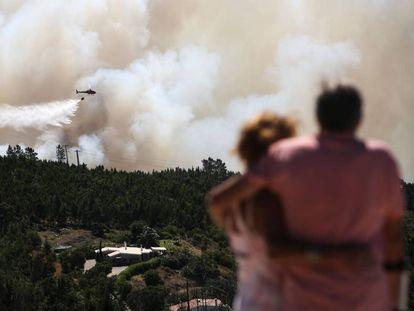 Una pareja contempla este miércoles cómo un helicóptero trabaja en las labores de extinción del incendio en el Algarve (Portugal).