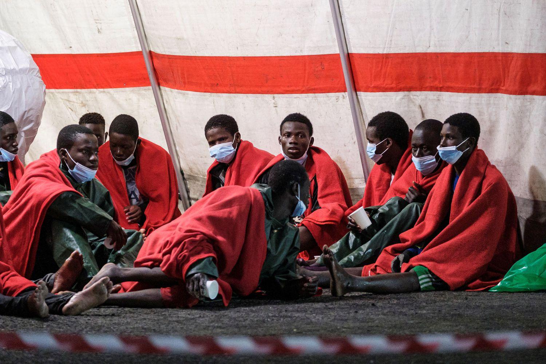 En la imagen, varios de los ocupantes del cayuco descansan en una tienda de campaña de Cruz Roja tras desembarcar en Arguineguín.