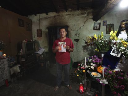 Clemente Rodríguez, padre del normalista identificado hace unas semanas. En la imagen, tomada en 2014, Clemente posa en su casa con una foto de su hijo.